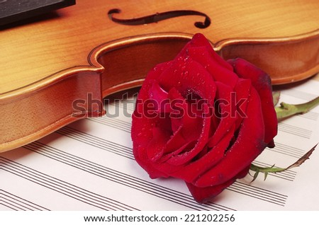 A violin, red rose and sheet music - stock photo
