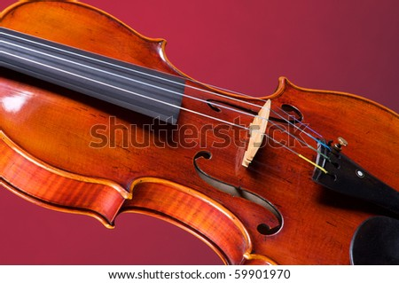 A violin viola isolated against a red background in the horizontal format with copy space. - stock photo