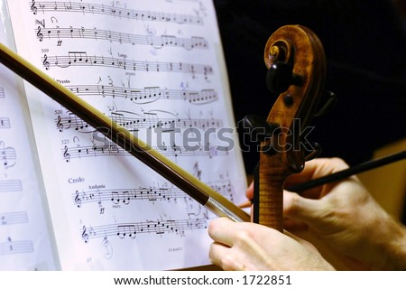 """A violinist hand with a violin, bow and a pencil, music of Puccini's """"Gloria"""" on background. - stock photo"""