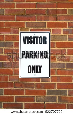 A visitor parking sign on a business exterior wall