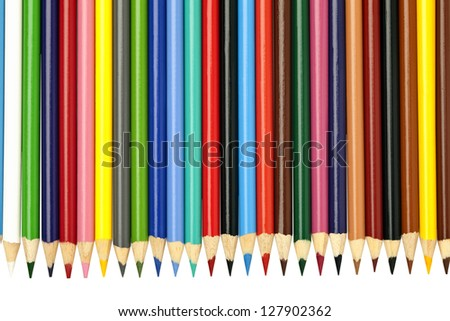 A vivid arrangement of brightly colored pencil crayons on a white background. - stock photo