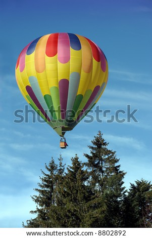 A vivid hot air balloon floating up beyond the trees. - stock photo