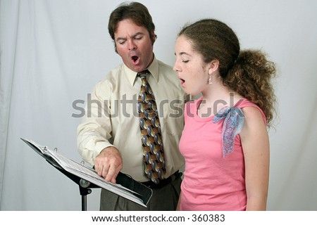 A voice coach and student singing together. - stock photo