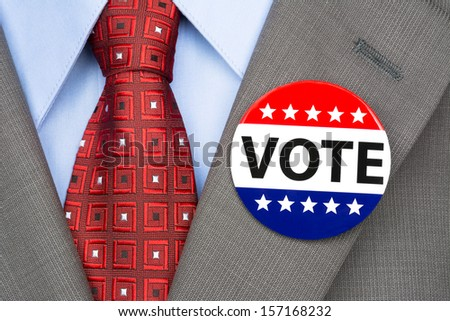 A voter wears a vote pin on his suit lapel during election season - stock photo