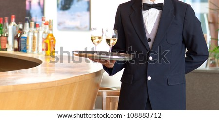 A waiter holding a tray with white wine glasses for serving - stock photo