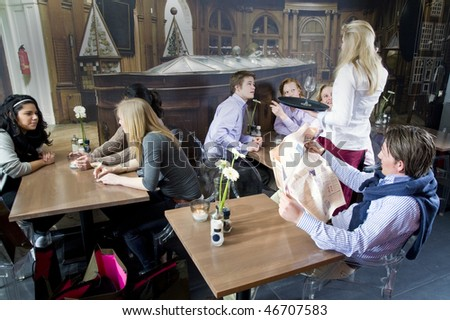 a waitress taking orders from her customers in a crowded restaurant - stock photo
