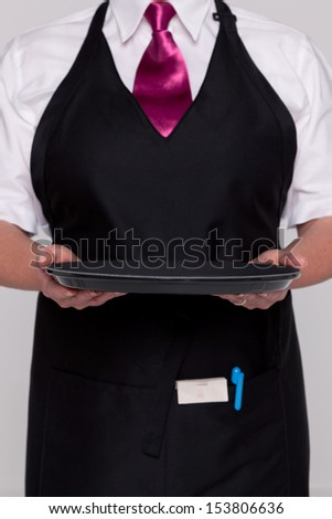 A waitress wearing an apron and tie holding an empty tray. Good image for product placement.. - stock photo