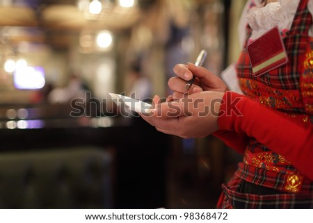 A waitress writing order at a restaurant - stock photo