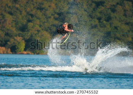 A wakeskater launches off the wake behind a boat. - stock photo