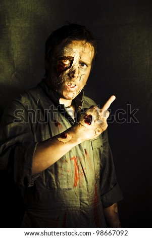 A walking dead zombie with decaying and rotting flesh gives a fingers up sign marking or singling out a person for their demise in a death threat concept - stock photo
