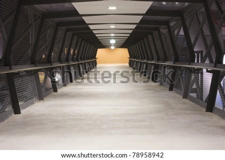 A walkway bridge with steel mesh walls on both sides - stock photo
