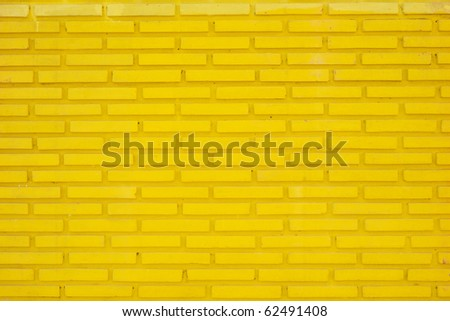 A wall of dirty yellow raised thin bricks - stock photo