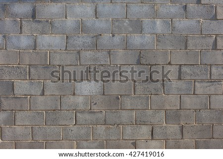 a wall of gray brick in the sunset