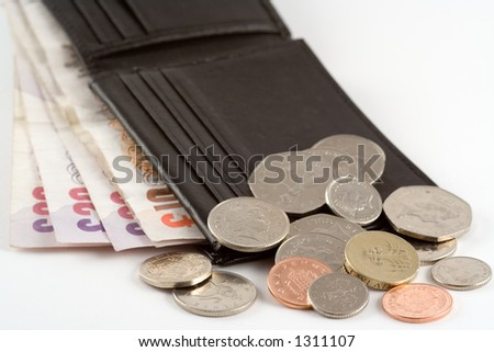A wallet full of notes with coins on top