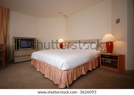 A warm and cosy bedroom ready for a tired guest - stock photo
