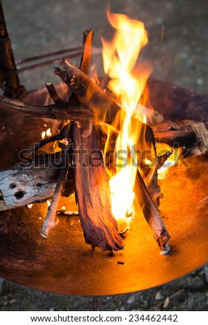 A warm, glowing campfire in the early evening. - stock photo