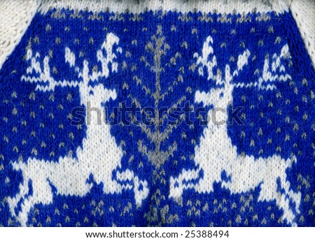 A warm sweater with two reindeer, fragments, closeup.