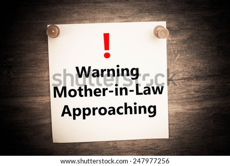 a warning of mother in law approaching  concept on note paper - stock photo