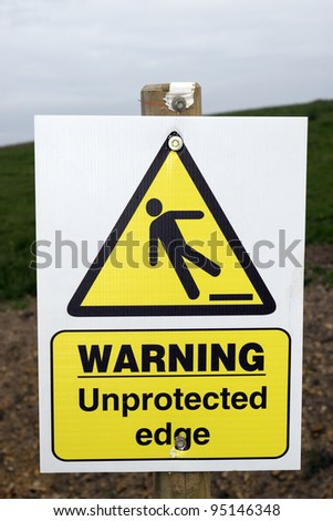a warning sign about an unprotected edge on a construction site with clipping path - stock photo