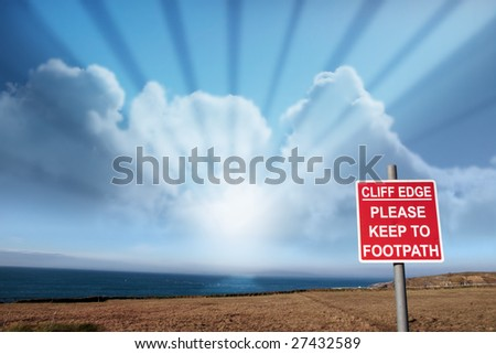 a warning sign of danger at the cliff edge - stock photo