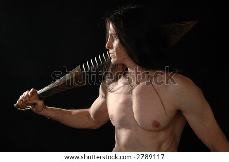 A warrior in the darkness iwth his sword drawn - stock photo