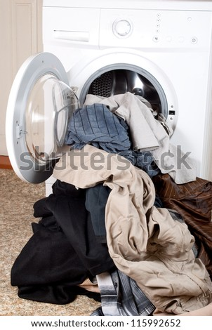 A washing machine and a big pile of laundry - stock photo