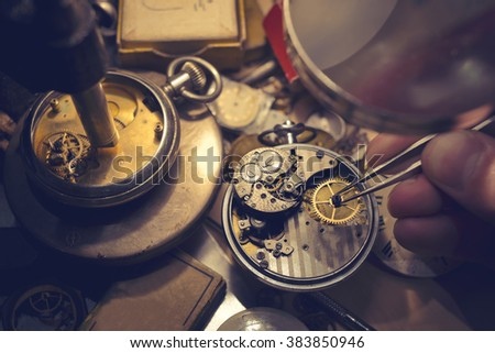 A watch maker repairing a vintage automatic watch. - stock photo
