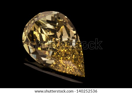 A waterdrop shaped yellow diamond isolated on black background