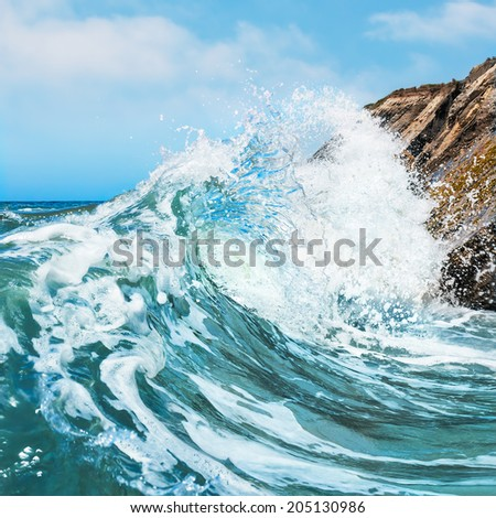 A wave crashing on the rocky shore at Gaviota State Beach in Central California. - stock photo