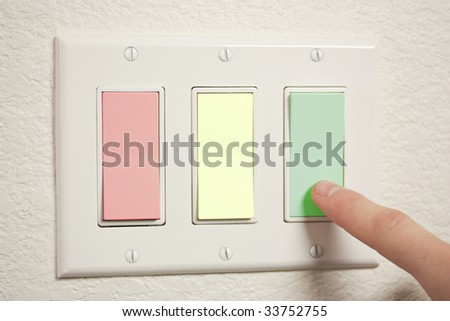 A 3-way switch, colored red, yellow, and green - stock photo