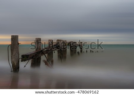 A weathered and broken pier located near Burlington, Ontario taken at sunset and twilight.