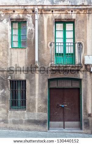 A weathered facade with a window, a balcony, a grilled window and a metallic door. The picture has been taken in the Sarri�  quarter of Barcelona, where old buildings and traditional facades abound. - stock photo