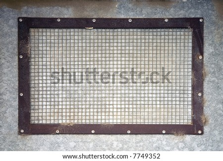 A weathered grid on a metal wall - stock photo