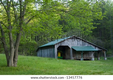 A Weathered Old Pole Barn With Green Roof In Pasture