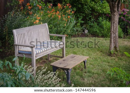 A weathered wooden bench with faded cushion and a rustic table sit invitingly in a secluded garden nook with a background of orange tiger lilies.  - stock photo