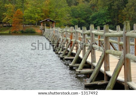 A weathered wooden foot bridge spans across a small lake . - stock photo