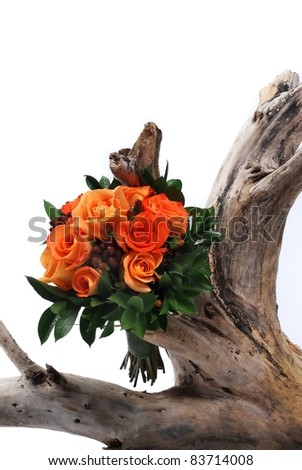 A wedding bouquet of flowers on white on tree stump - stock photo
