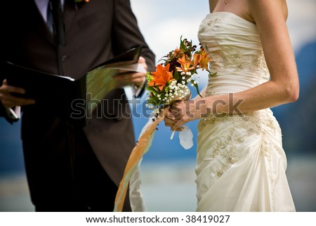 A wedding ceremony by the lakeside with the bride and the minister - stock photo