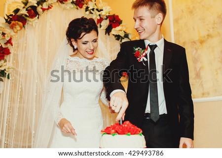 A wedding couple smiles while cutting a wedding cake behind an altar - stock photo