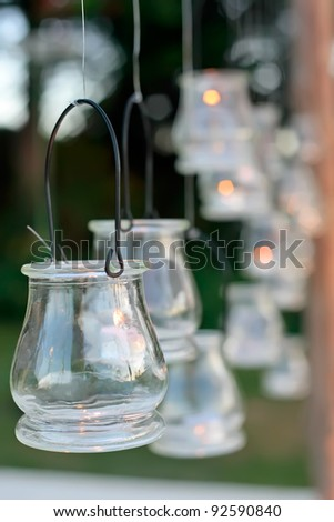 A wedding reception decorated with candles hung in the trees