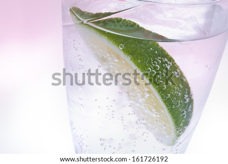 A wedge of lime floating in a glass of clear carbonated beverage. - stock photo