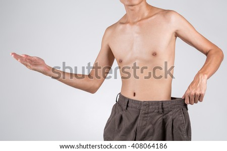 A weight loss male shows his old jeans with welcome hand up, isolated on background