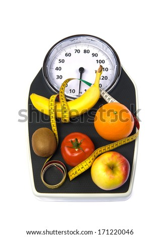 A weight scale with fruit and measuring tape - stock photo