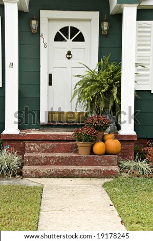 A welcoming entryway with a boston fern, mums and a pumpkin. - stock photo