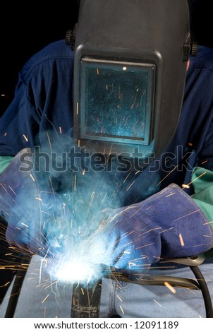 A welder fabricates a tool by attaching two pieces of metal.