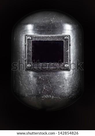 A welders Helmet front view, low key lighting. - stock photo