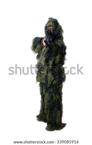 A well armed man wears a Ghilly Camouflage Moss style suit to stay hidden from the enemy or prying eyes while hiding in the woods. Ghilly Suits are used by Snipers and Hunters to blend into the woods  - stock photo
