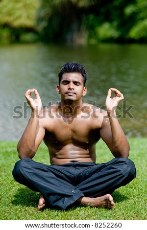 A well-built Asian man practicing yoga outside by water