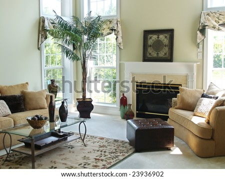 A well decorated family room in a modern american home with an overstuffed sofa, chair and glass coffee table. Large windows make the room very bright and airy. - stock photo