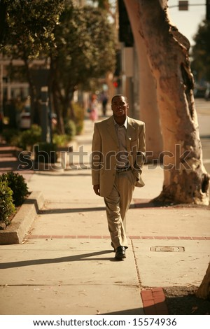 a well dressed african american male model walks down a city sidewalk as if he is walking down a cat walk at a fashion show